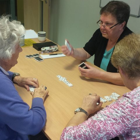 volunteer playing dominoes with members of the games group
