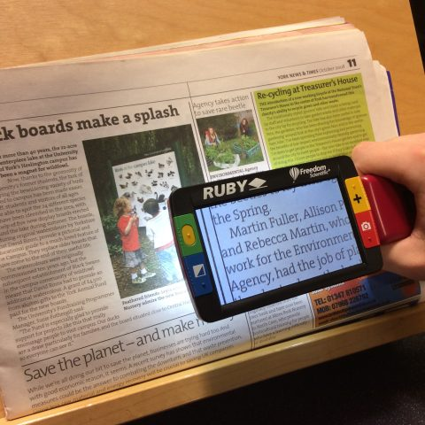a Ruby magnifier used to read a newspaper